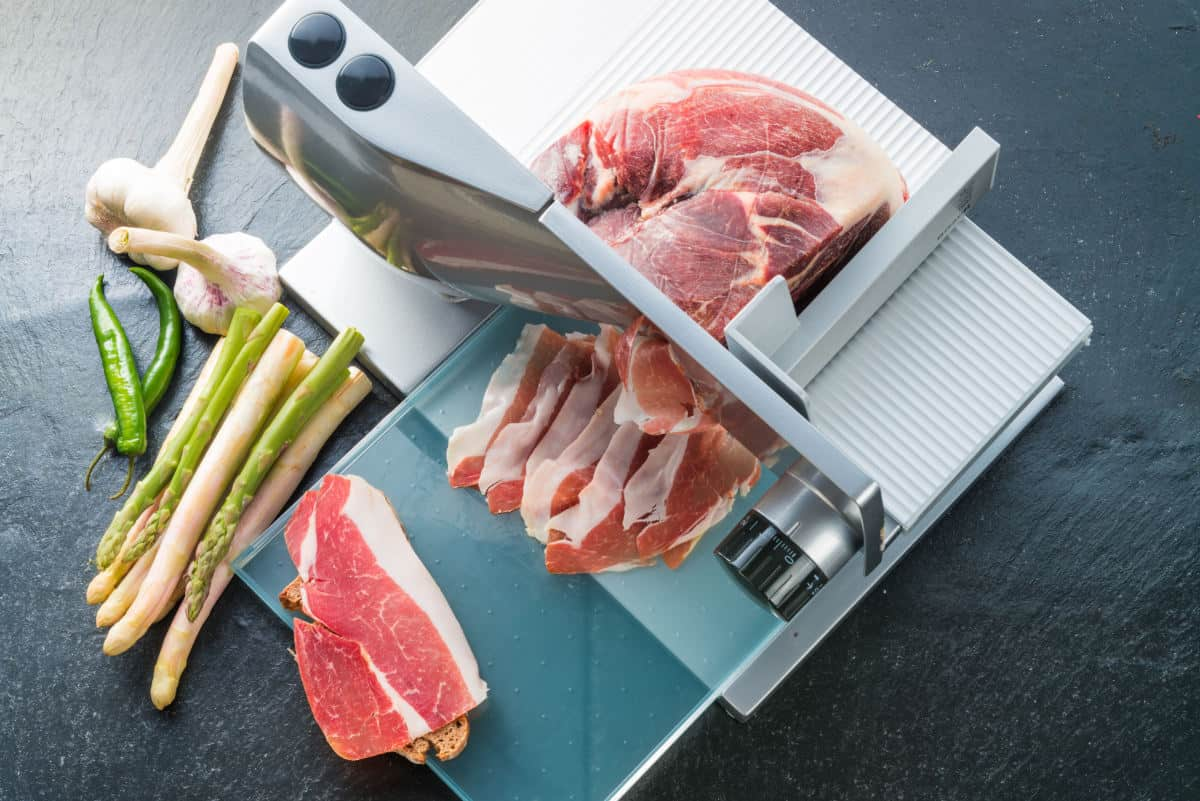 Bacon being sliced in a food slicer, with some garlic and spring onions in shot