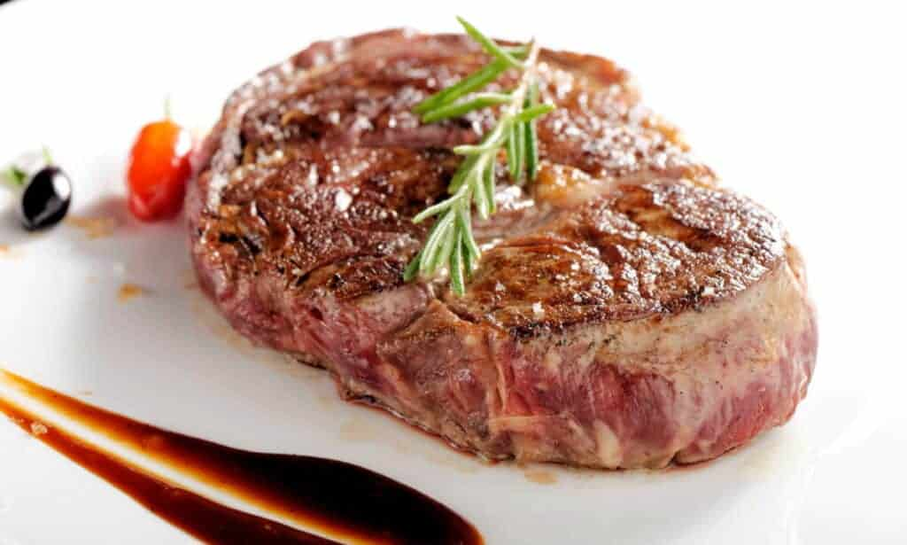 Grilled bottom round steak on a white plate with a smear of sauce and some rosemary