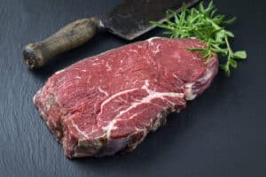 Raw bottom round steak, on a slate cutting board with rosemary and a butchers knife