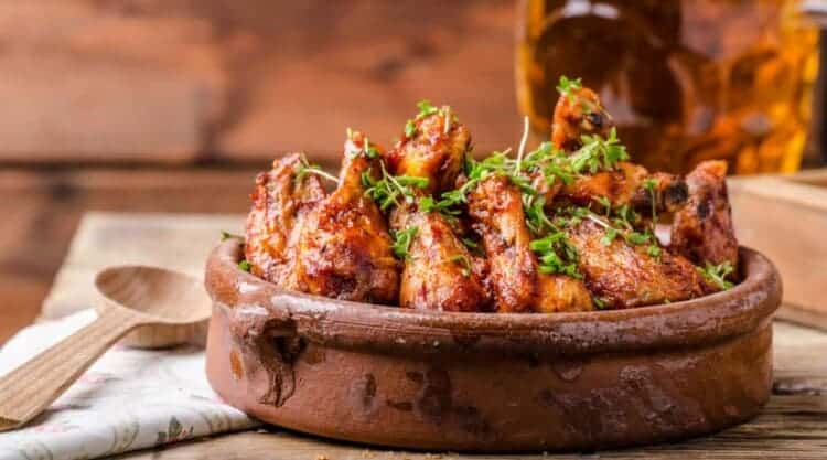 A bowl full of chicken wings with crispy skin