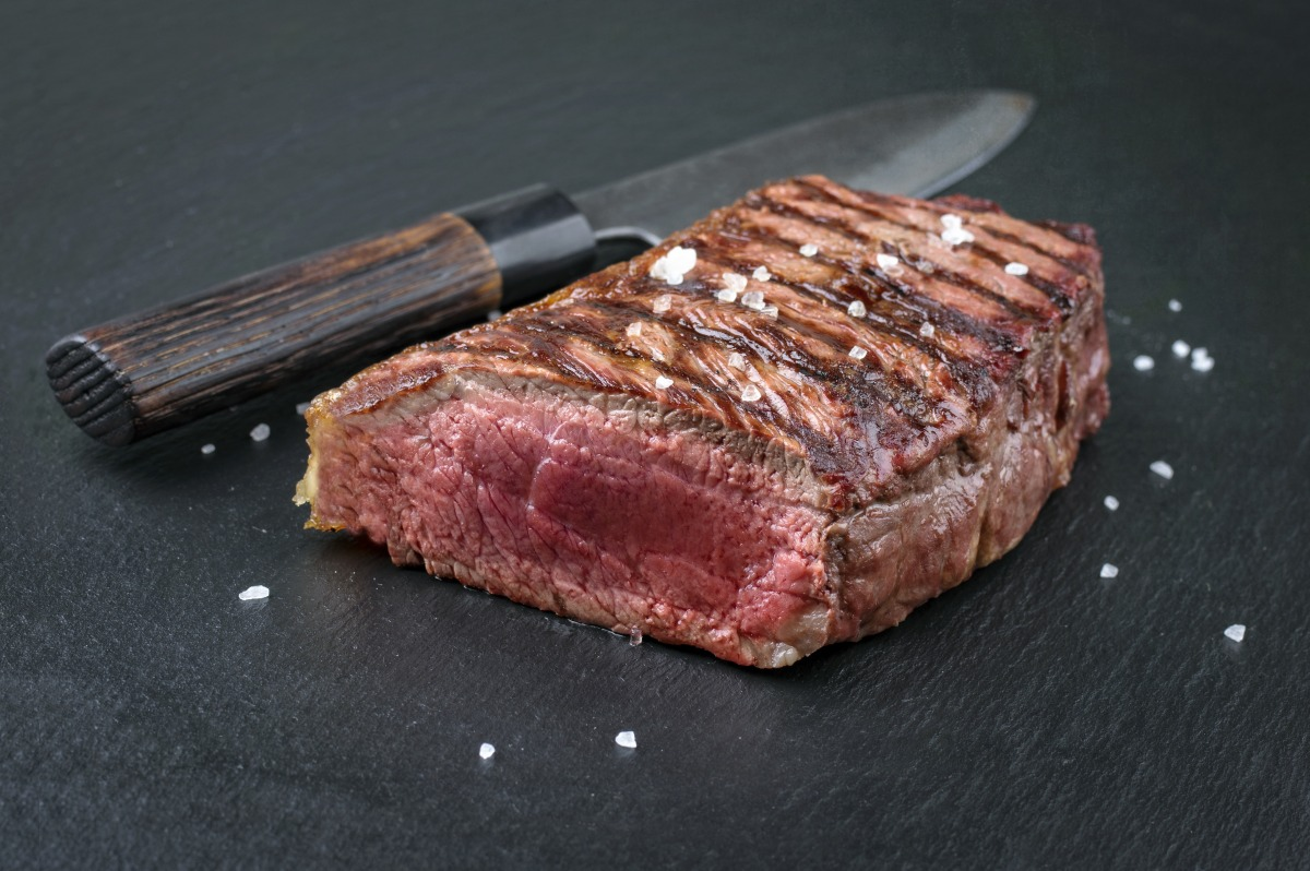 grilled bottom round steak with end sliced off, sitting on a slate surface