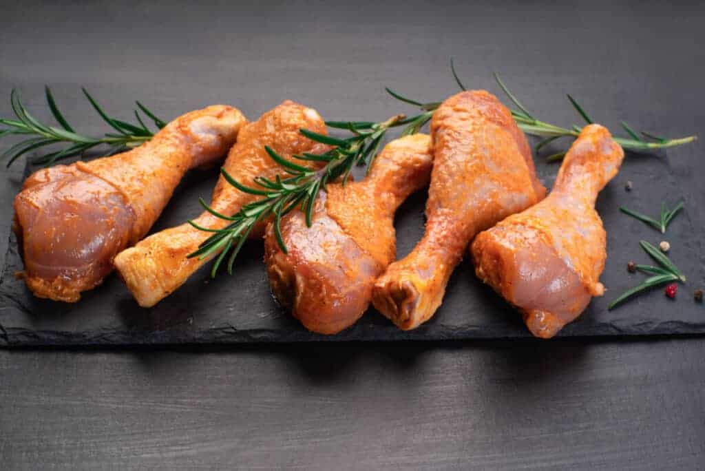 Marinated chicken legs on slate board with some herbs layed on top