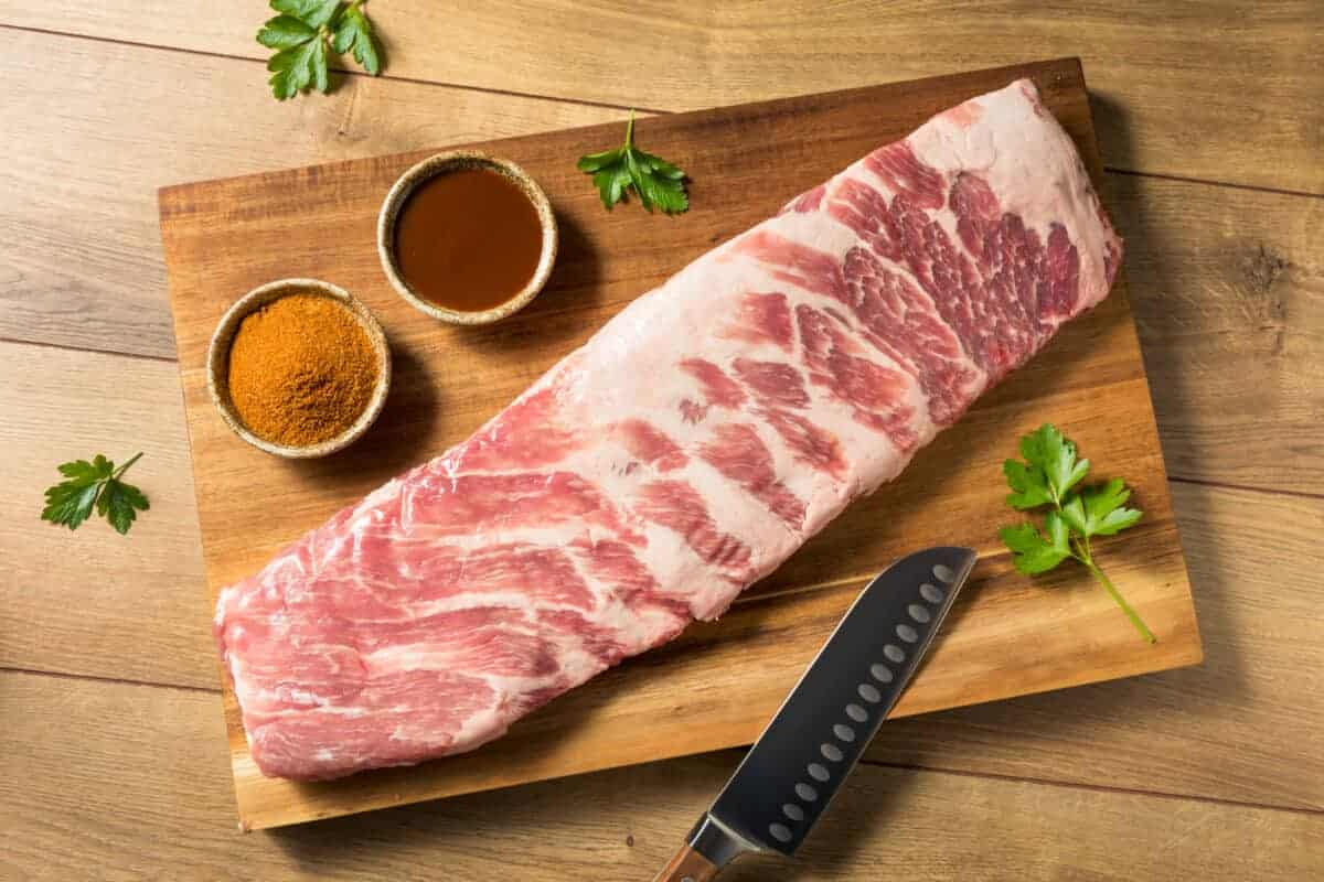 raw st louis ribs on a cutting board with two ramekins full of spices