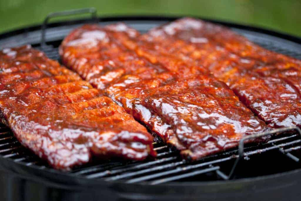 Sauced st louis ribs sitting on a charcoal grill