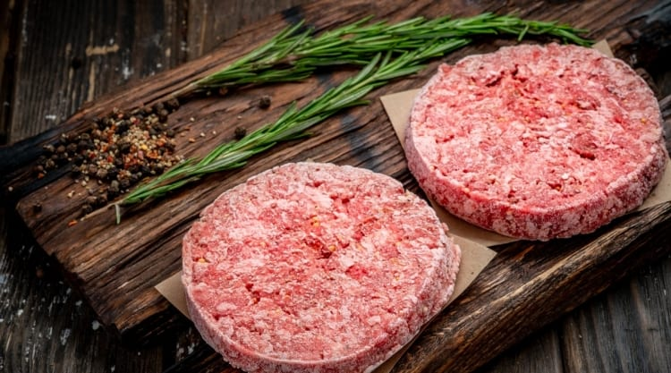 frozen burgers on cutting board with a rosemary sprig in the background