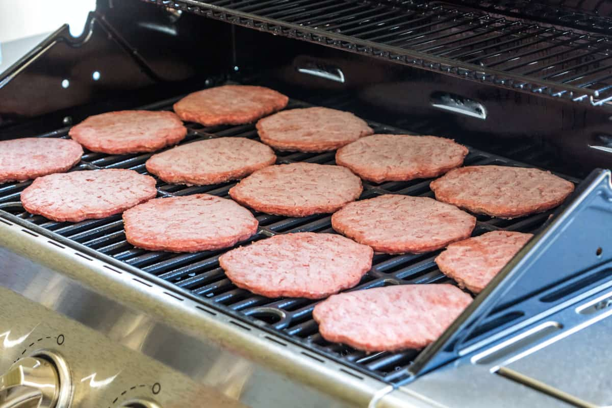 15 frozen burgers laid out on a gas grill