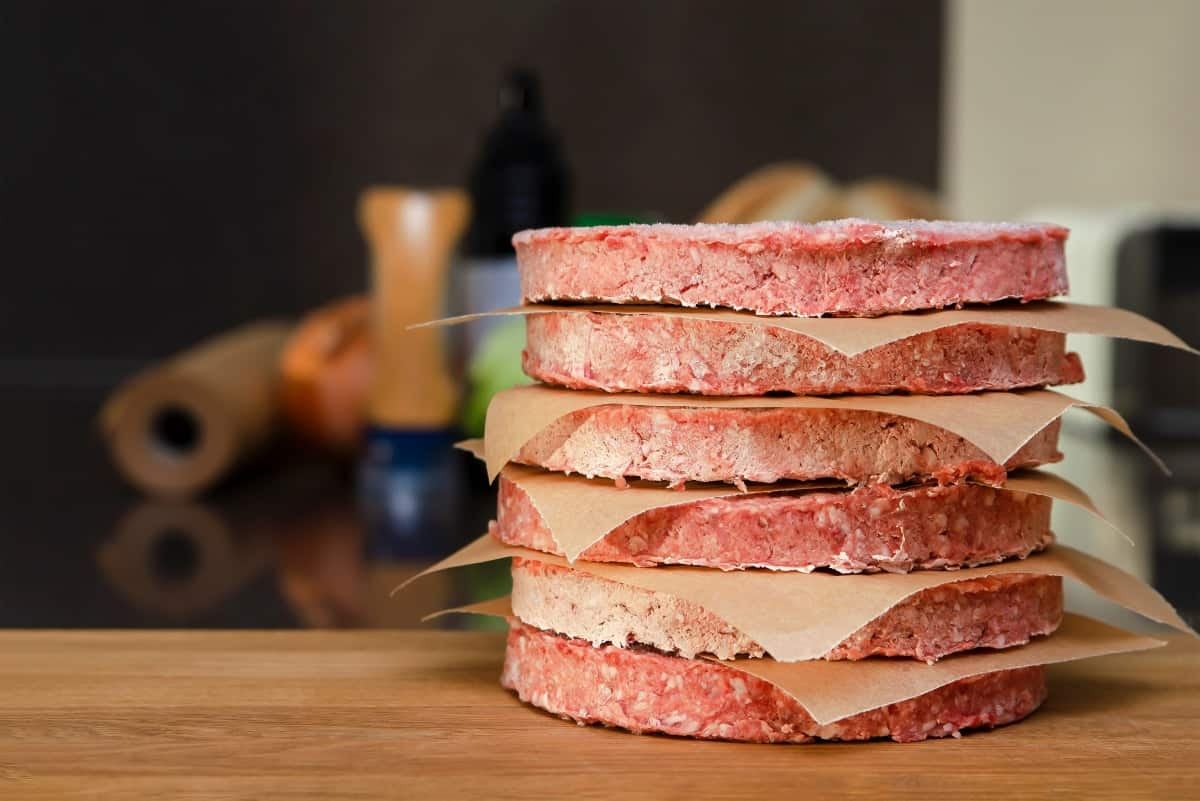A stack of frozen burgers separated by parchment squares