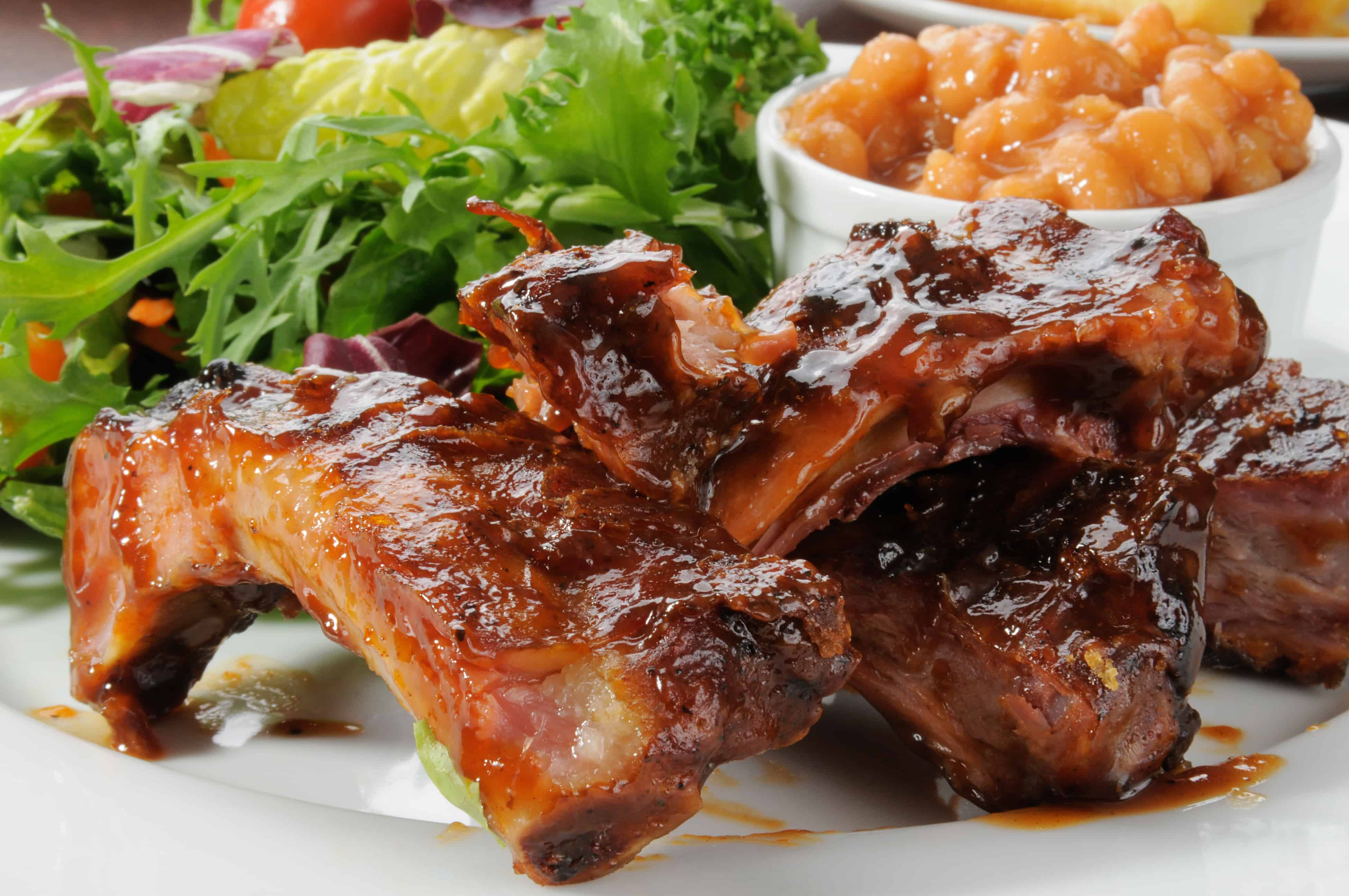 Close up of baby back ribs, slathered in sauce, in front of a pot of beans and some green salad