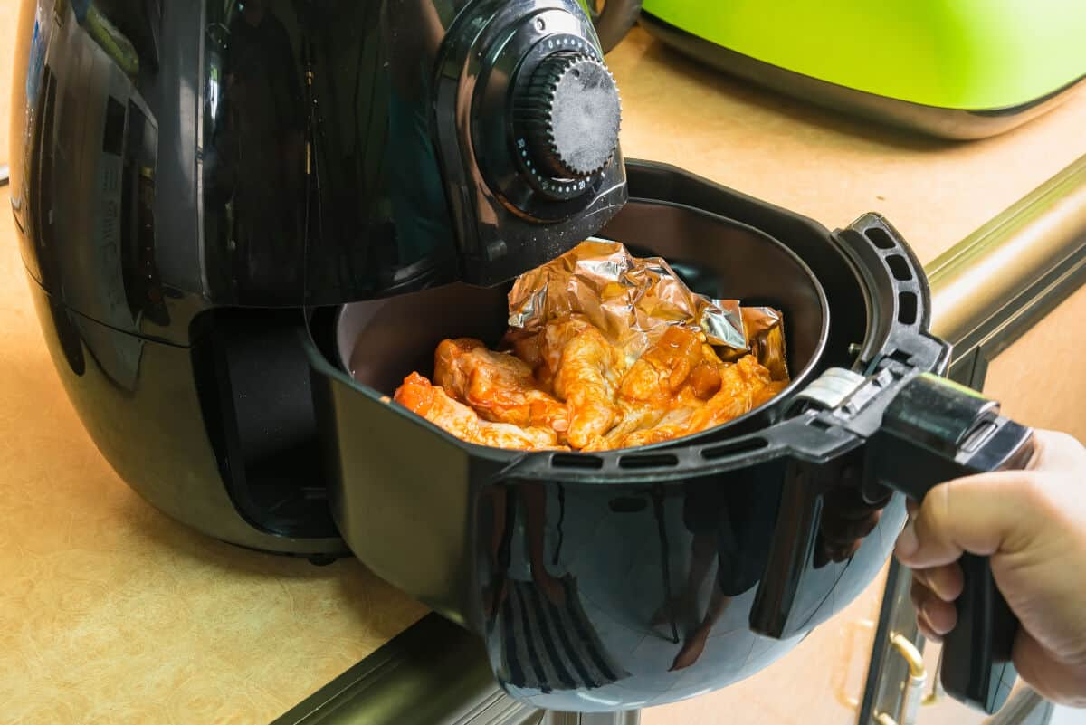 Chicken wings being placed into an a black air fryer on a wooden surface