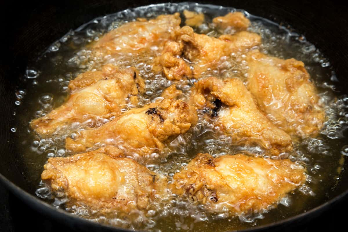 close up of chicken wings in a deep fryer, with oil bubbling