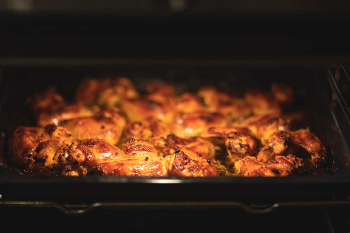 Chicken wings being reheated in an oven