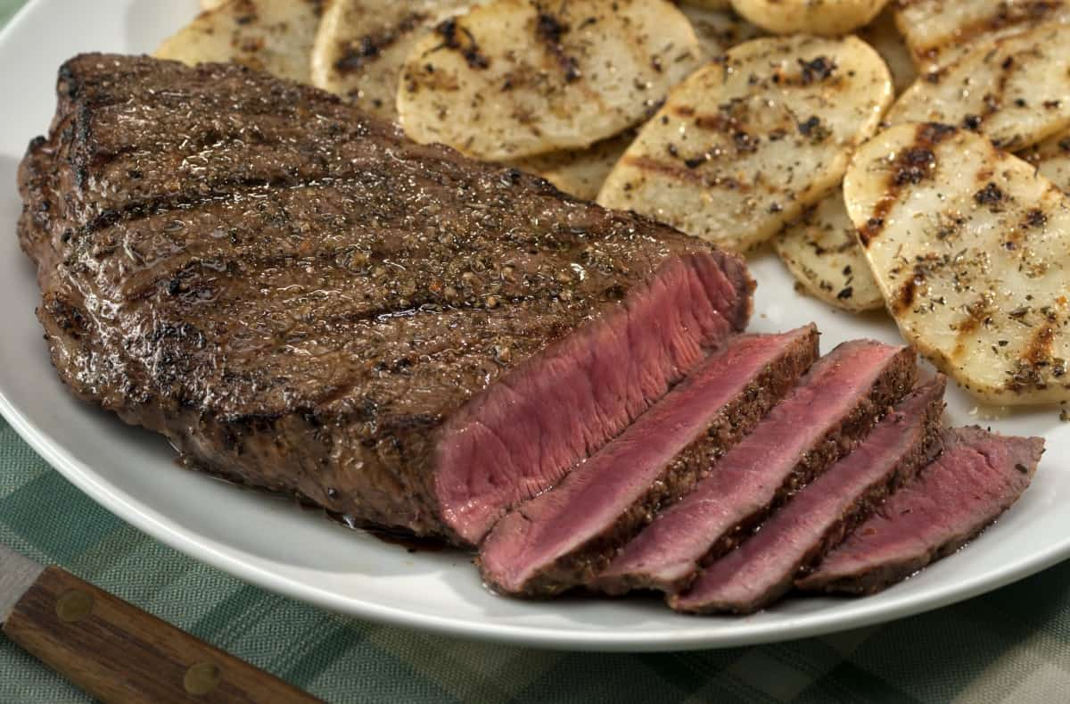 grilled and sliced top round steak with thin grilled potatoes