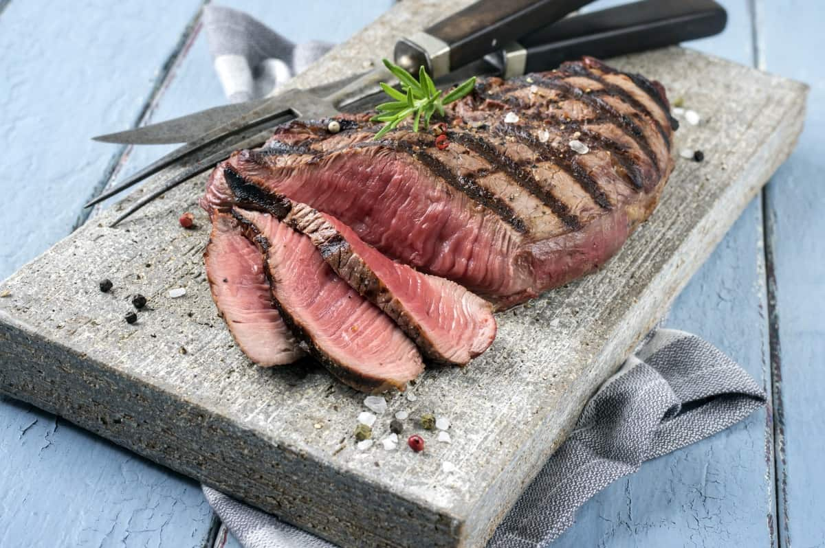 sliced grilled top round steak on a stone platter, with a carving knife and fork and a sprig of rosemary on top