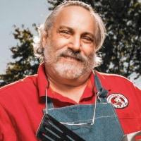 Head and shoulders shot of Meathead Goldwyn in red shirt and blue apron