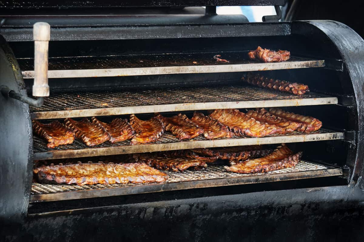 A large smoker with 4 levels of grates full of ribs