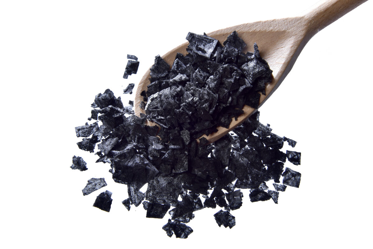 A spoon full of Cyprus black flake salt isolated on white
