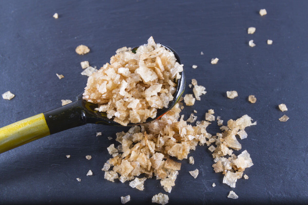 A spoon full of smoked sea salt, some spilled onto the table