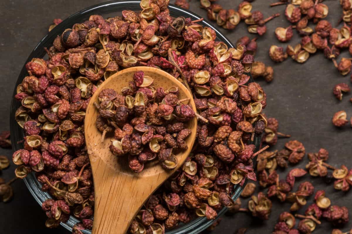 A pile of Szechuan peppercorns, with some held in a wooden spoon