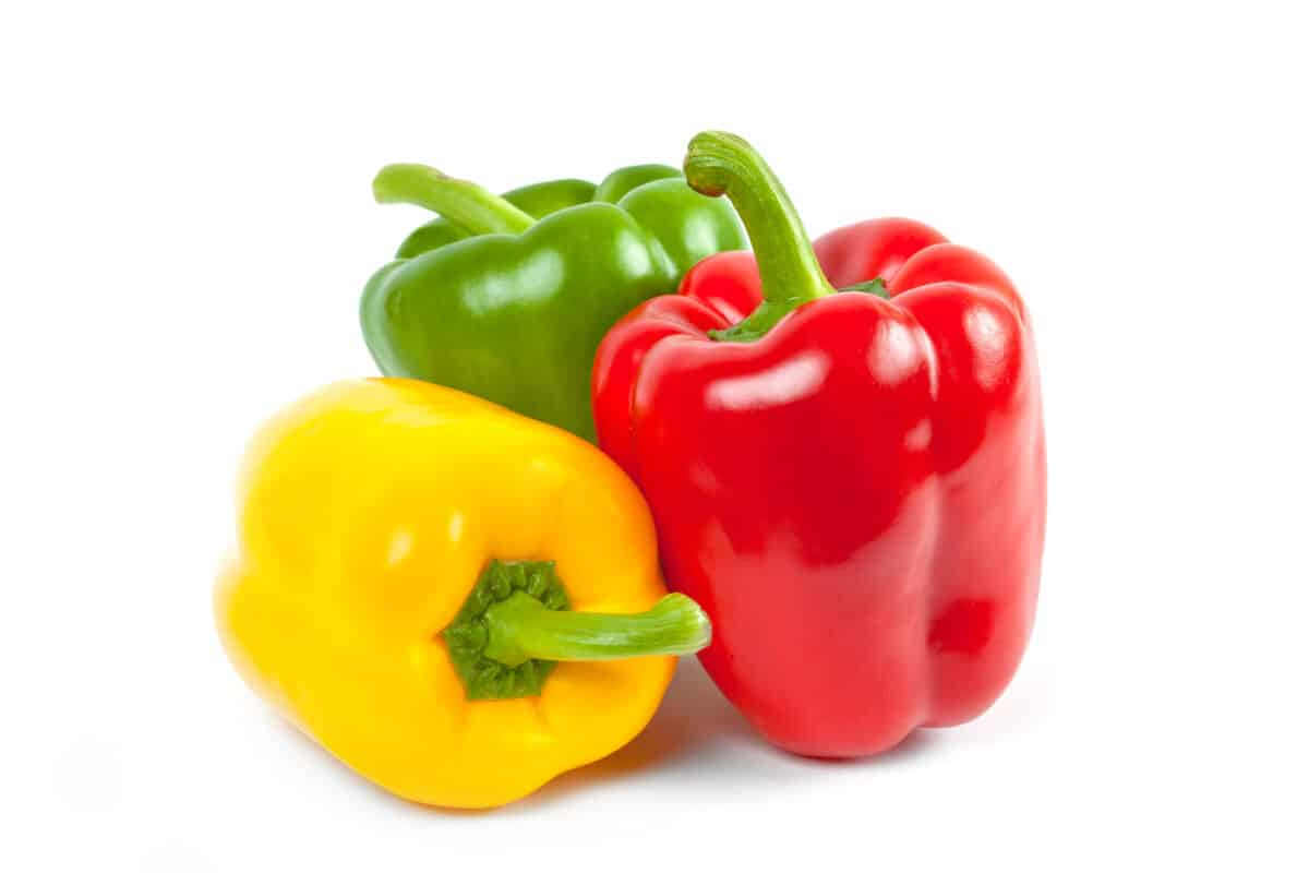 One each of red, yellow and green bell peppers isolated on white