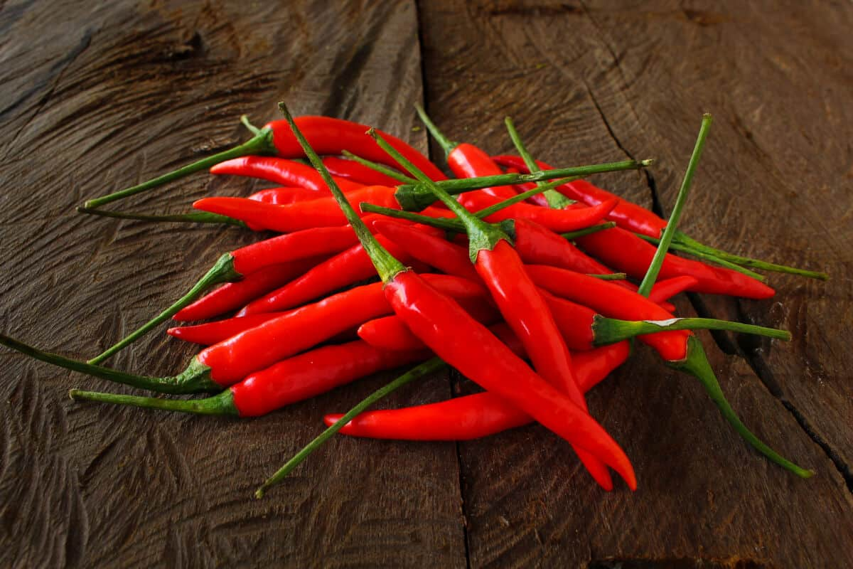 A pile of birds eye chilis on a wooden table