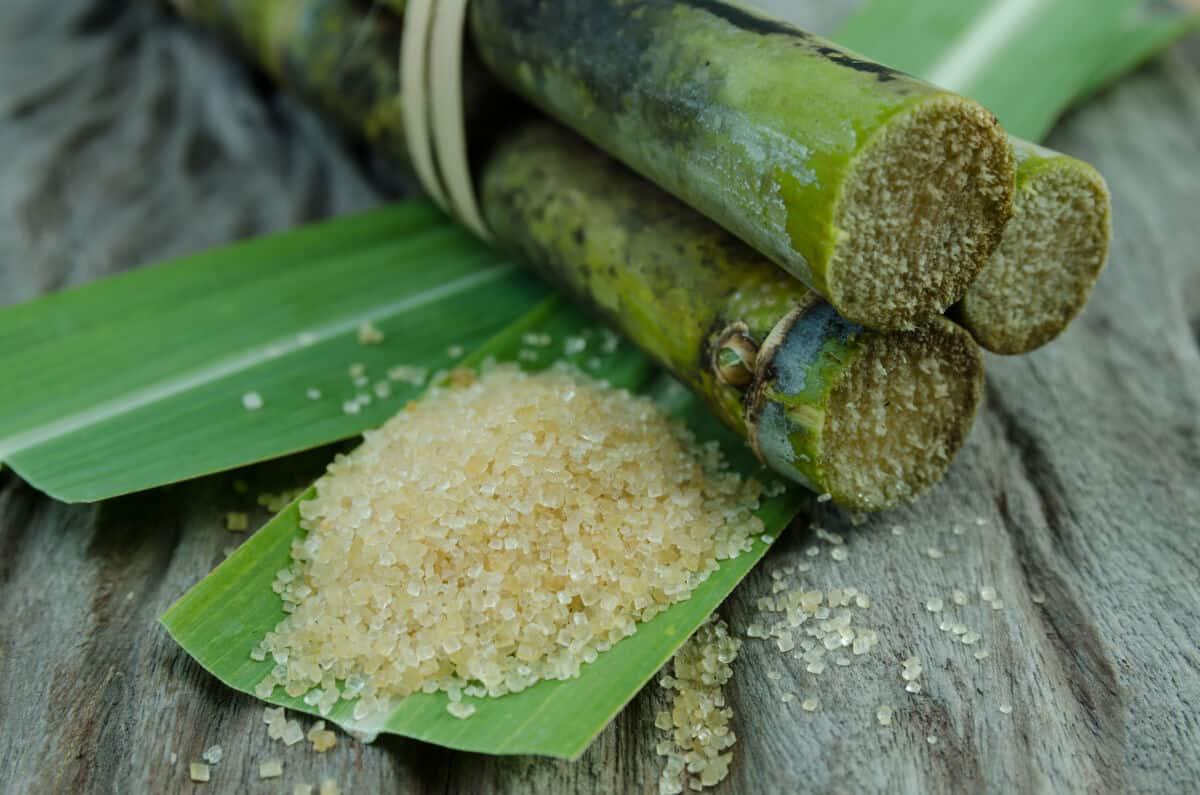 Cane sugar on a cane leaf, next to some sugar cane segments