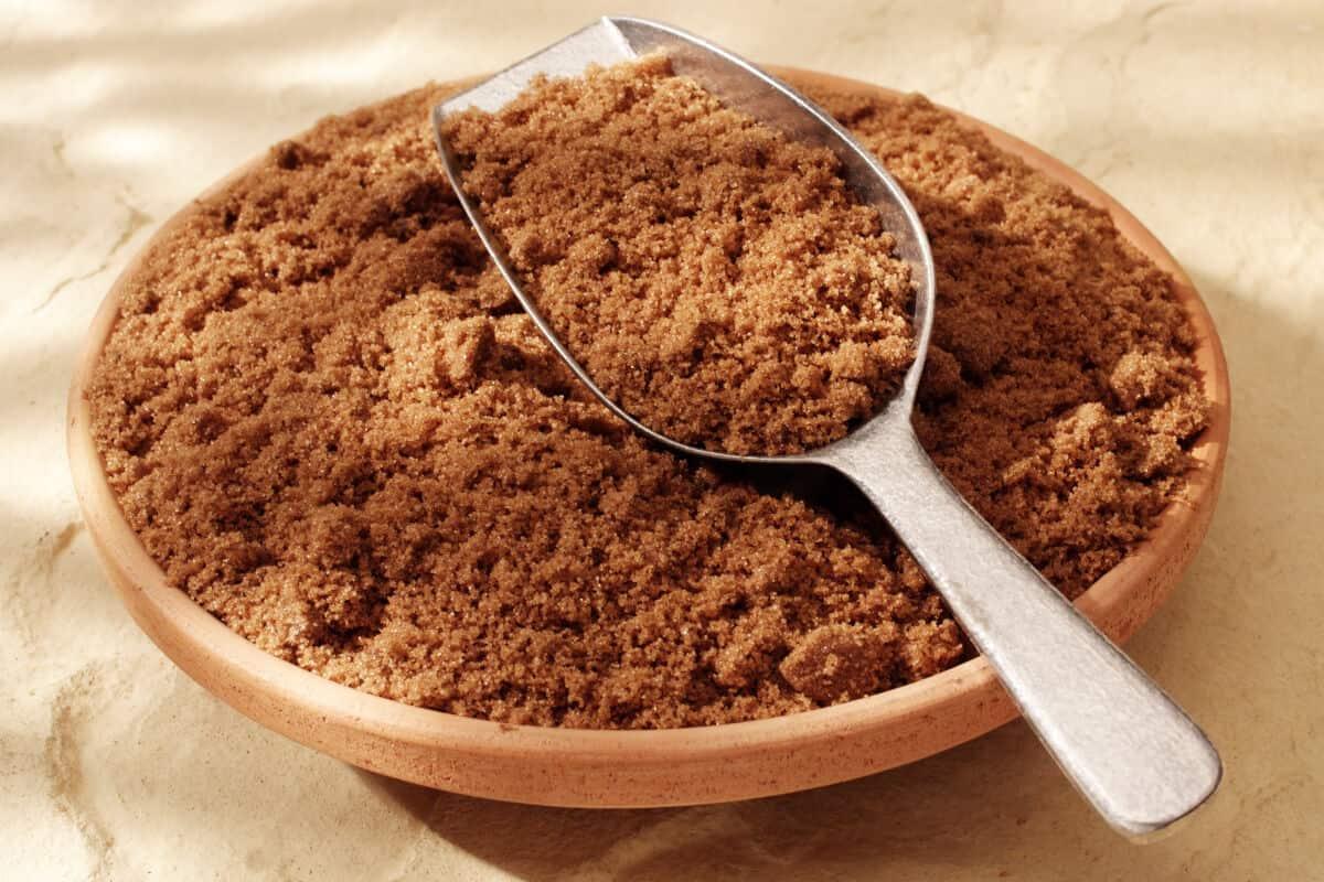 A metal scoop full of dark brown sugar in a wooden bowl