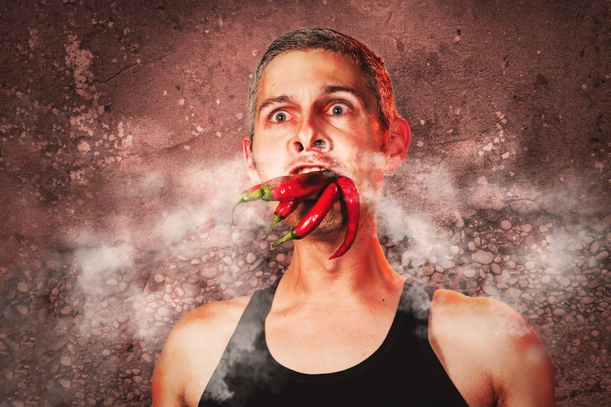 Mock up photo of man with chilis in mouth, and steam coming out of his hot looking face