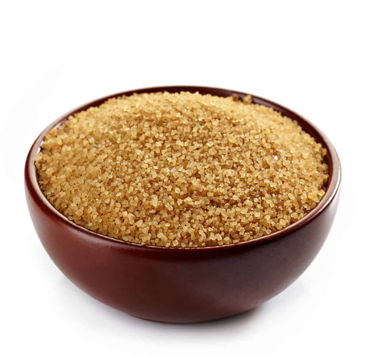 A brown bowl full of granulated brown sugar isolated on white