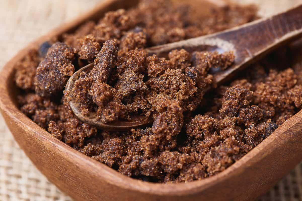 A square wooden bowl full of dark muscovado sugar