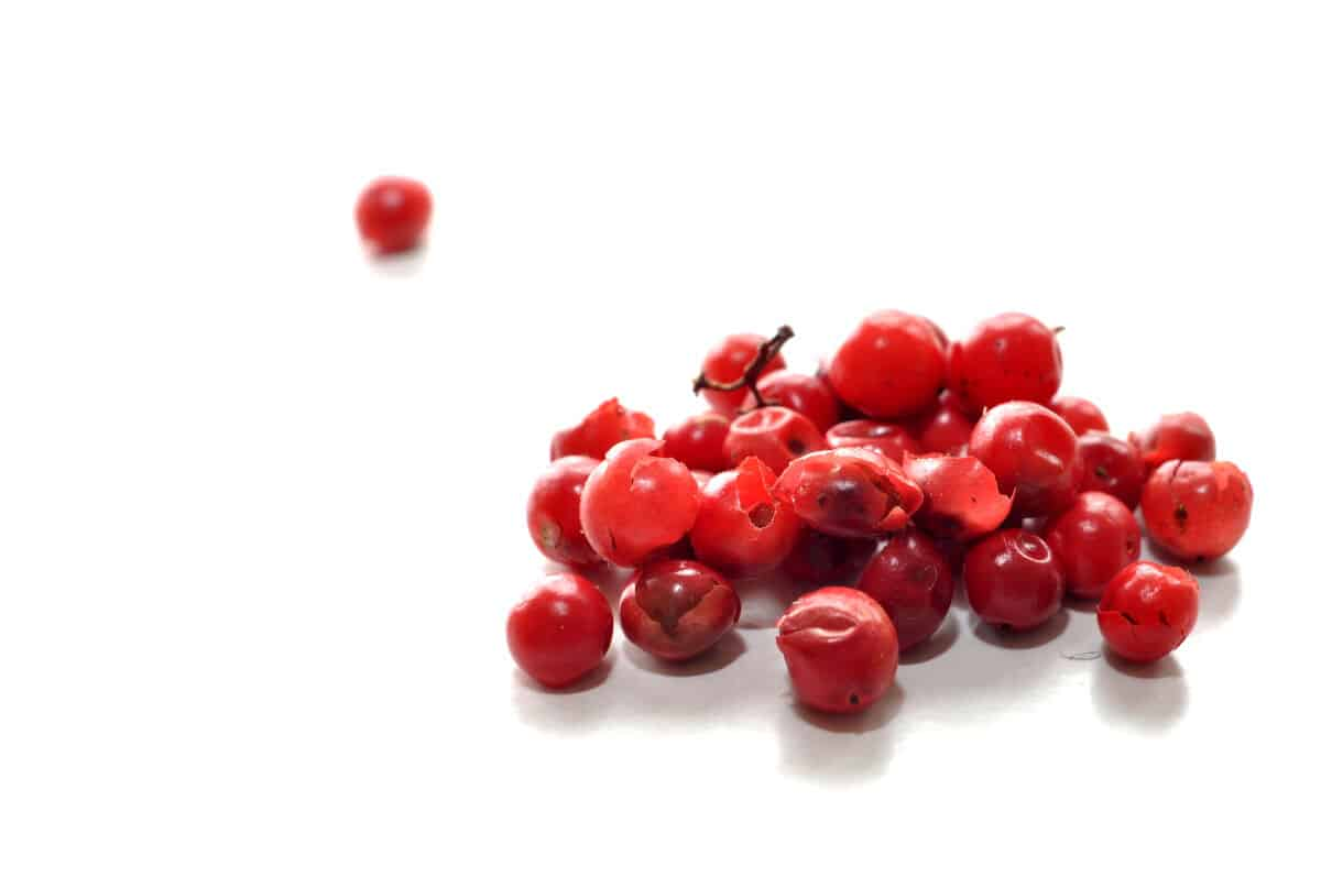 A small pile of red peppercorns on a white surface
