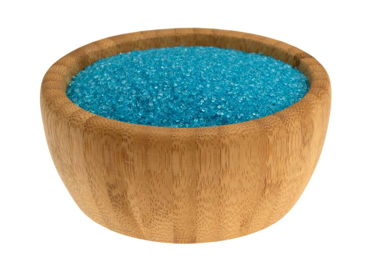 A wooden bowl full of blue sanding sugar isolated on white