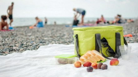 A soft-sided cooler bag, on a towel on a beach, with bread and fruit beside it