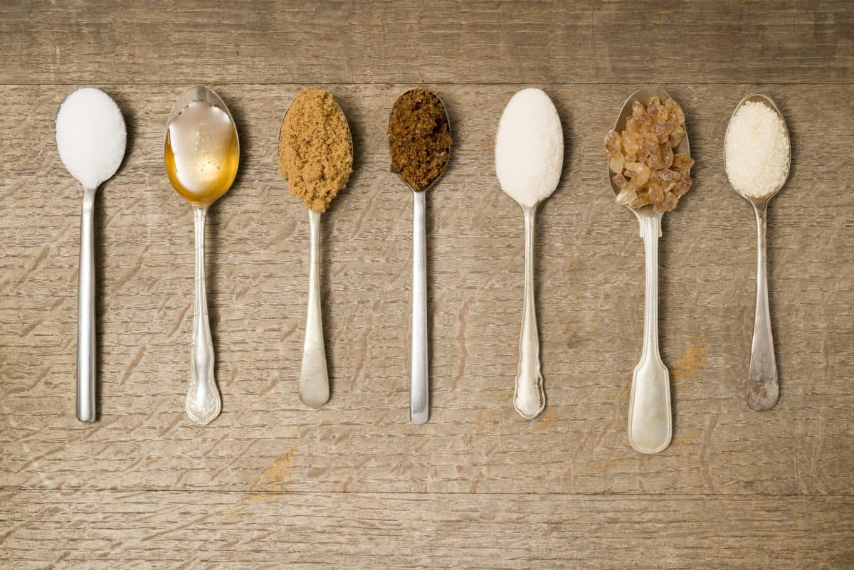 7 lined up teaspoons full of different types of sugar