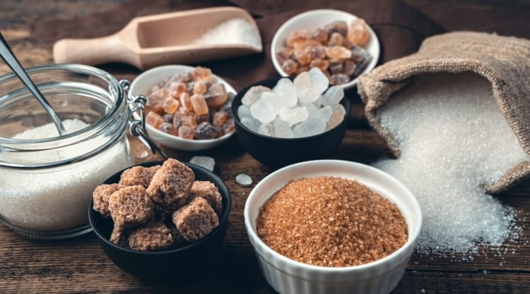 Many different types of sugar, in bowls, in a sack, spilled onto a table and more