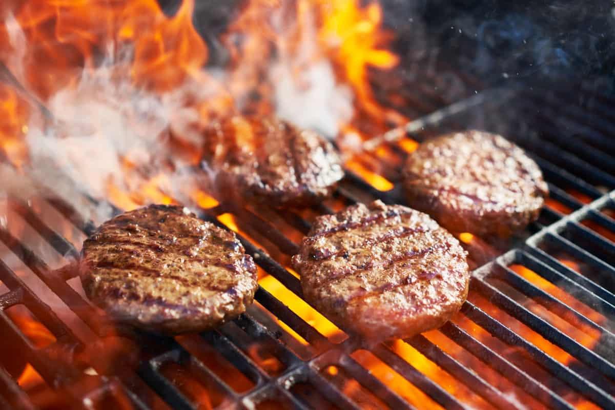 A few burgers grilling over big flames