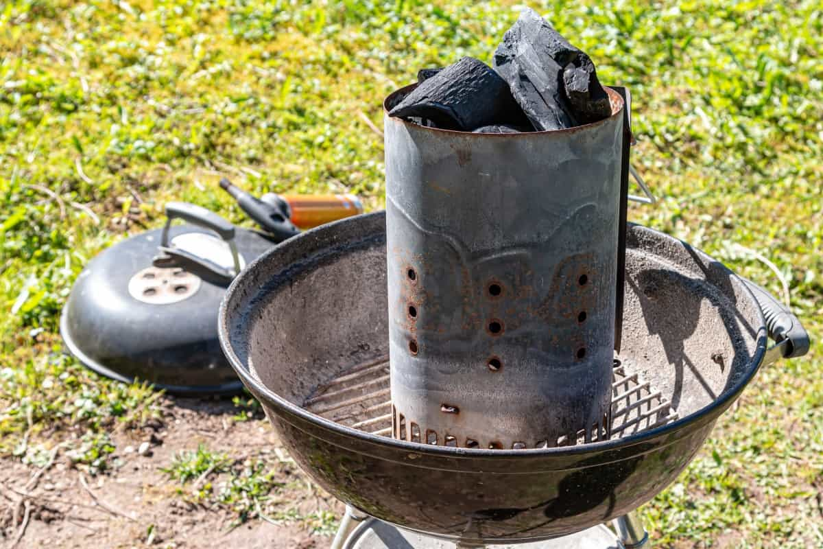 A charcoal chimney starter full of lumpwood charcoal in a kettle grill
