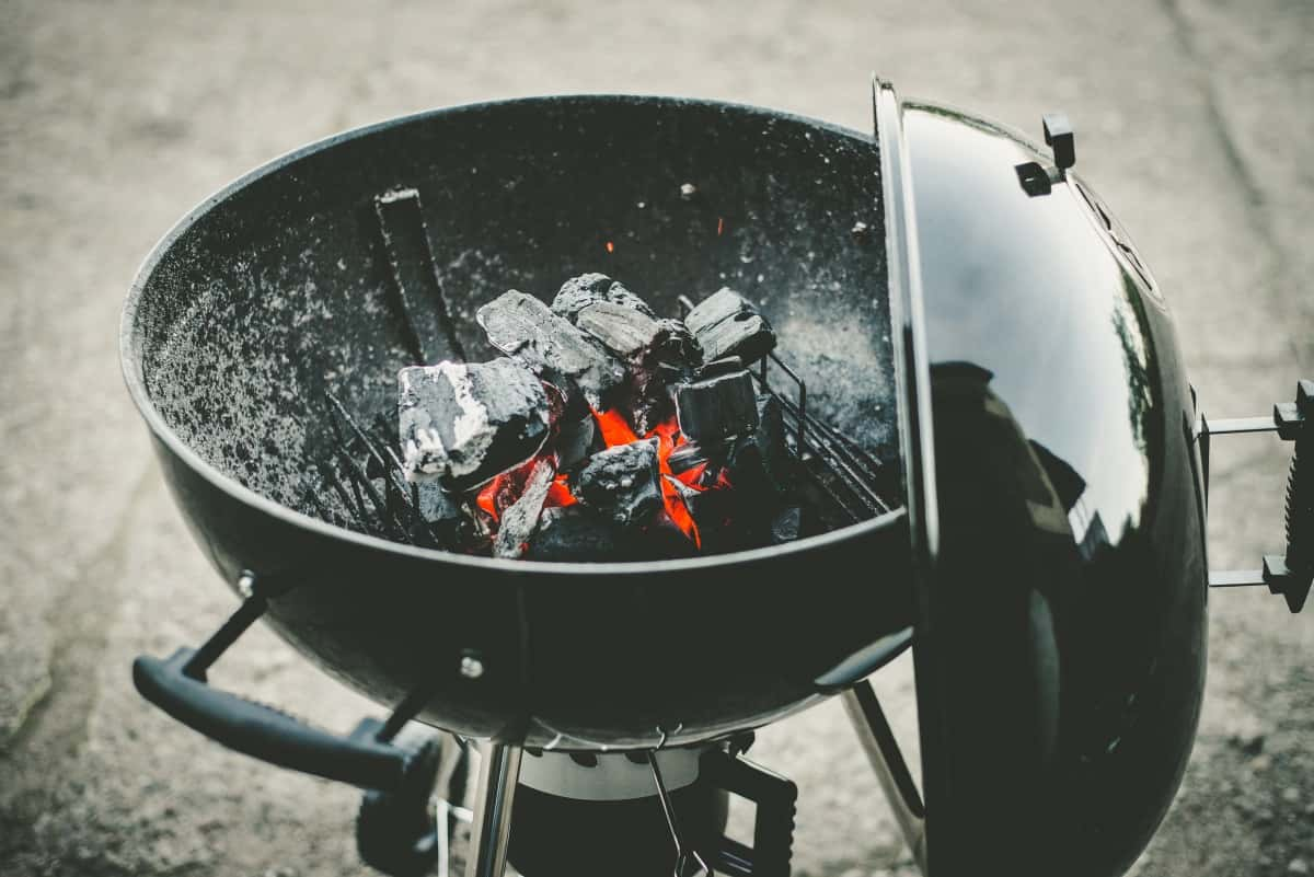 A black kettle style charcoal grill with lit coals in ,and lid hanging on the side of the bowl