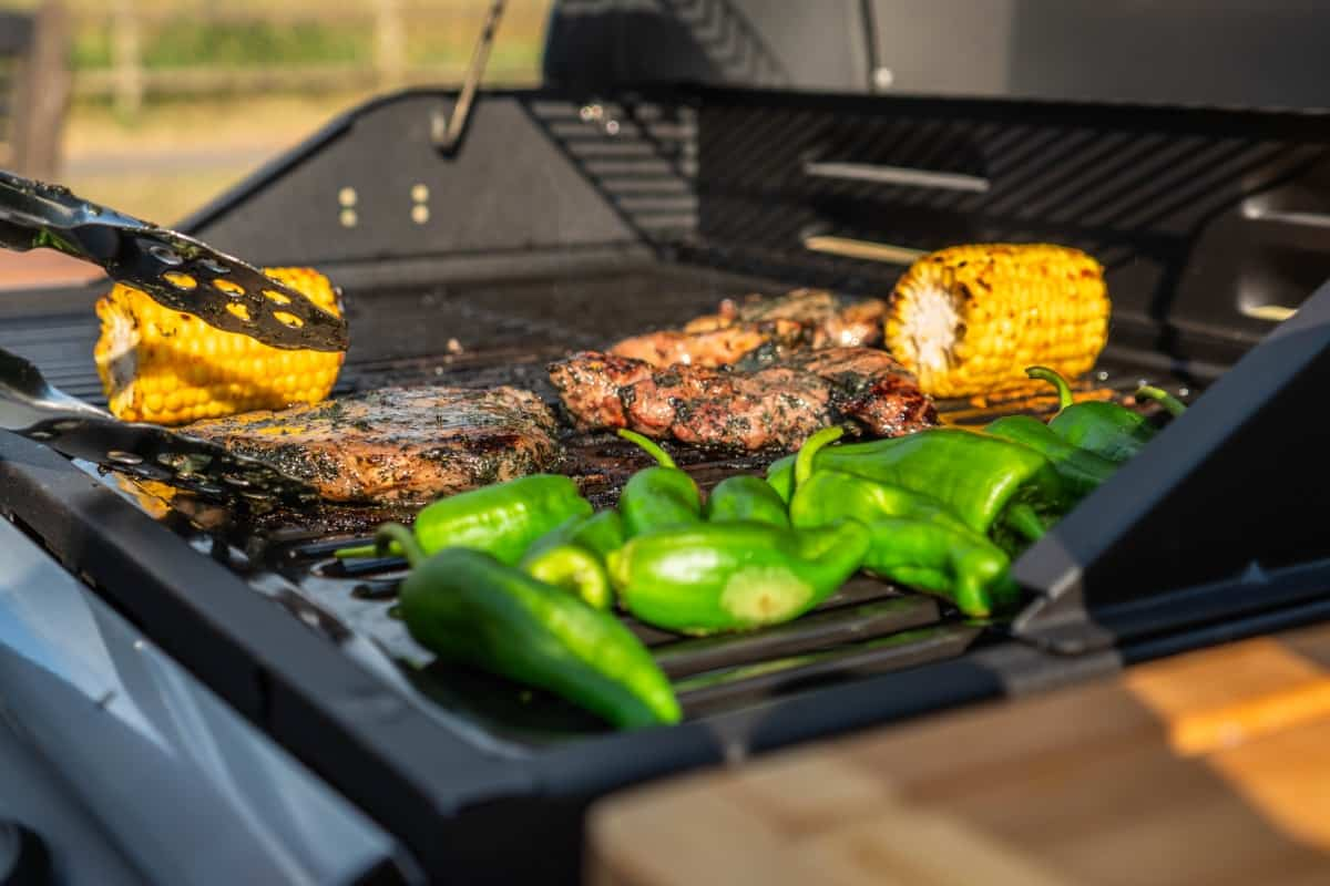 a grill full of colorful corn, meat and veg