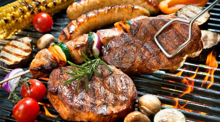 An array of meat, vegetables, corn and kebabs on a grill