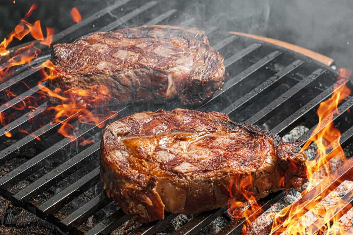 Two large pieces of meat on a flaming grill