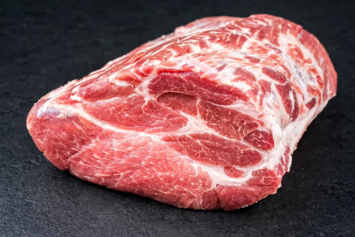 A raw pork boston butt on a dark surface