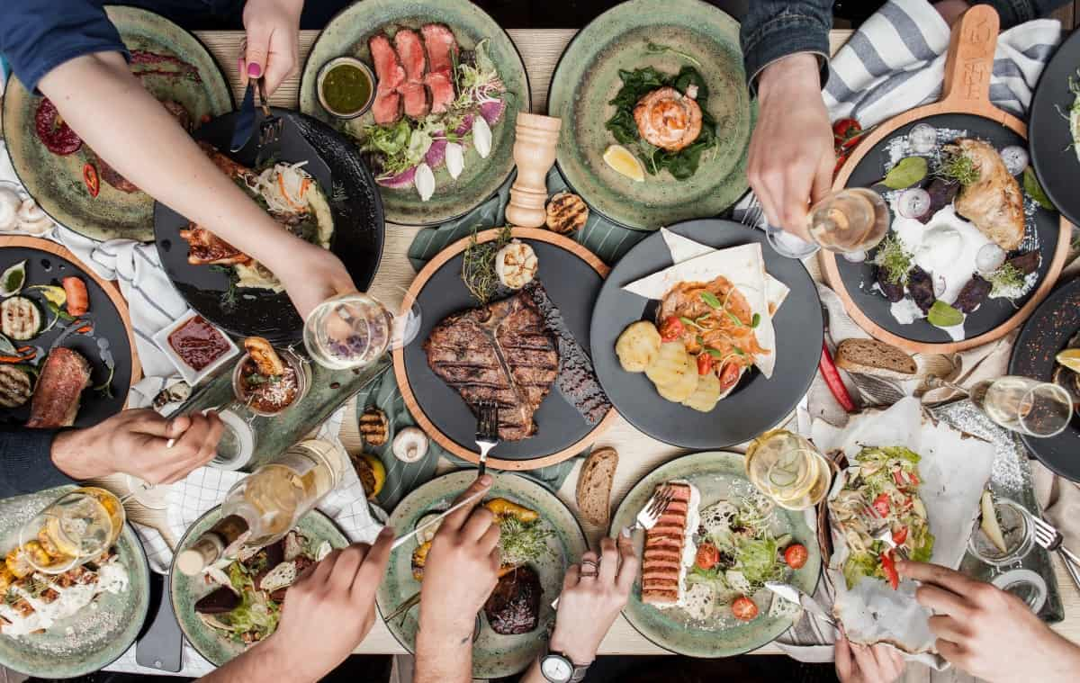 Overhead view of a table full of grilled food on plates
