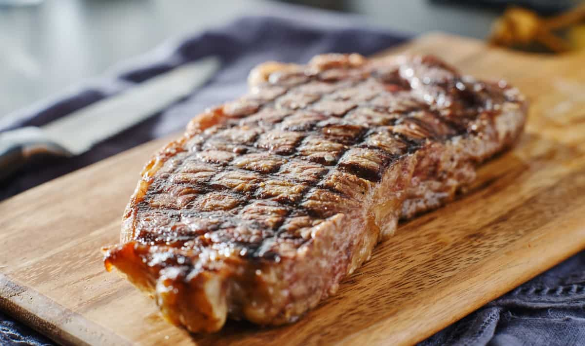 A grilled NY Strip steak resting on a cutting board