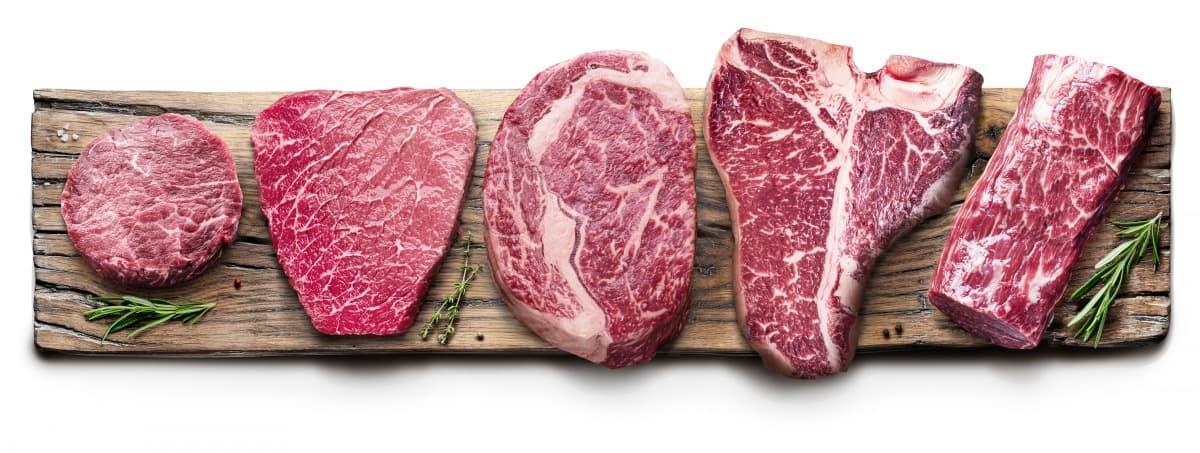 Different raw steaks spread across a long cutting board