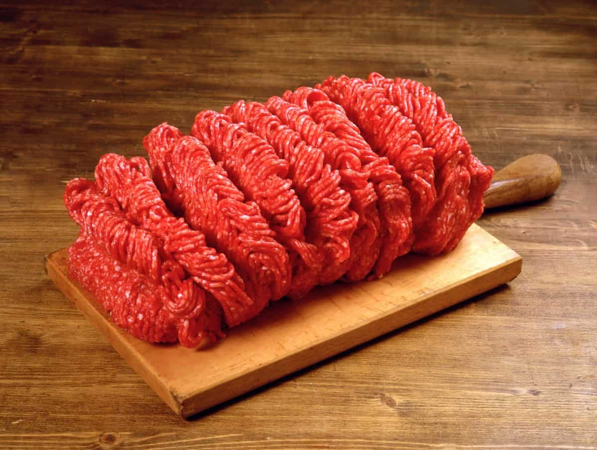ground beef on a wooden paddle with handle