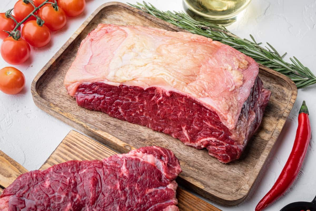 Large piece of raw short loin on cutting board with a steak sliced off