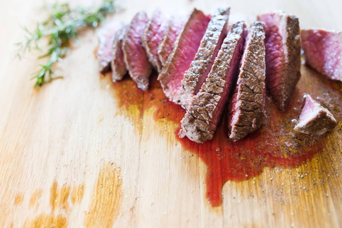 A sliced steak with juices running on cutting board
