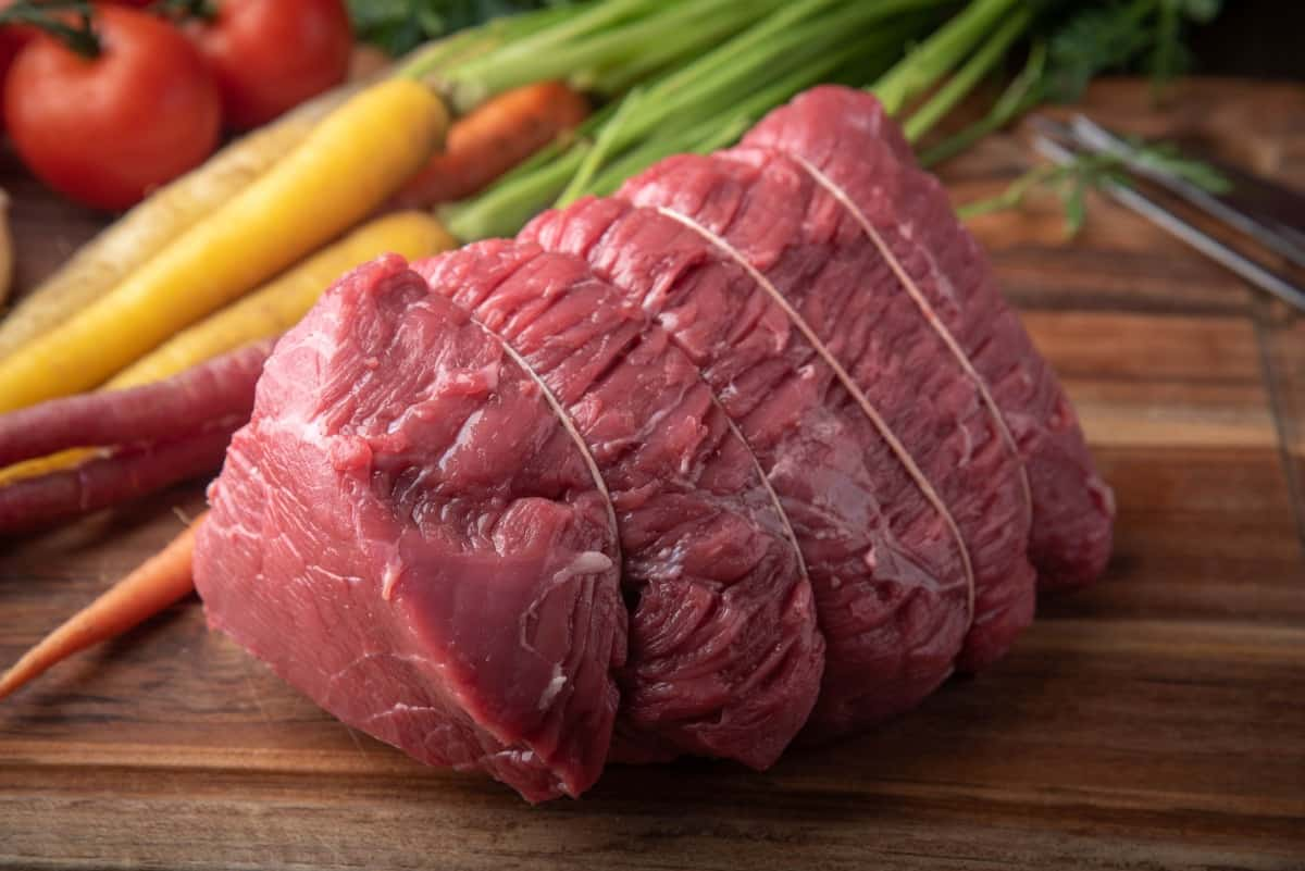 A tied top round roast with carrot sin the background