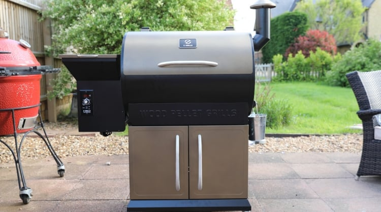 The Z Grills 700D pellet grill sitting on a patio next to a kamado grill