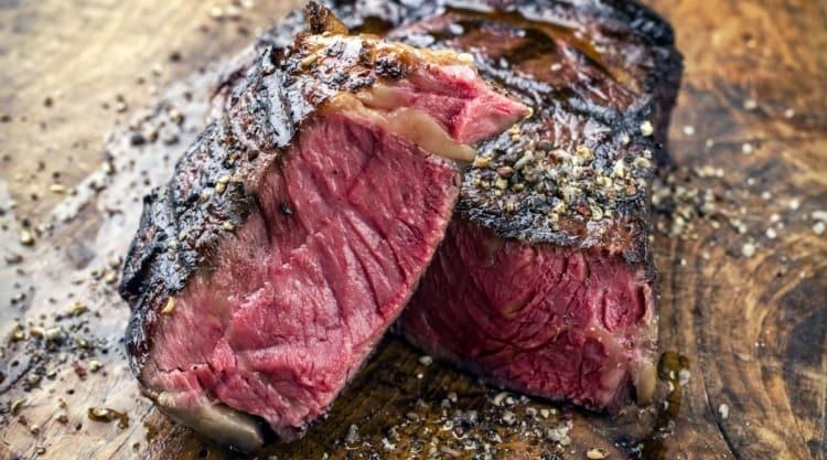 A blu rare, grilled wagyu ribeye steak cut in half